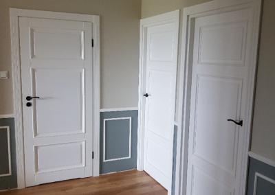 Białe uniwersalne drewniane drzwi w części komunikacyjnej
