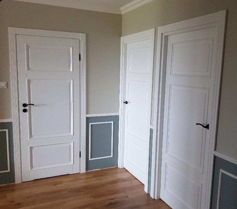 Białe uniwersalne drewniane drzwi w części komunikacyjnej domu